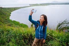 Hiker woman takes photographs self portrait Stock Image