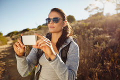 Hiker woman taking photographs with her smartphone Royalty Free Stock Images