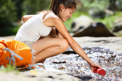 Hiker woman taking water in river in Yosemite Royalty Free Stock Photography