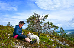 Hiker woman. On top of mountain with her dog Stock Image