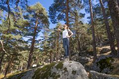 Hiker woman top of rock hand on her forehead looking at Royalty Free Stock Photos