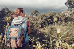 Hiker woman traveler with backpack looking at wild jungle. Stock Photography