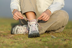 Hiker woman tying shoelaces of boots Royalty Free Stock Images