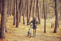 Hiker woman walking with a bicycle in the forest Royalty Free Stock Images
