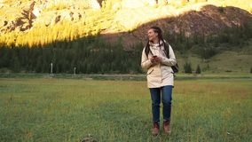 Hiker woman walking on field chat using smartphone stock video