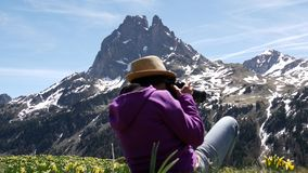 Hiker woman walking in the french Pyrenees mountains, Pic du midi d Ossau in background