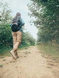 Hiker woman walking on path in summer forest Stock Photos