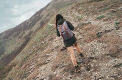 Hiker woman walking up mountain Royalty Free Stock Photos