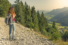 Hiker woman watching the landscape. Hiker woman with a backpack watching the landscape from a mountain Royalty Free Stock Photos