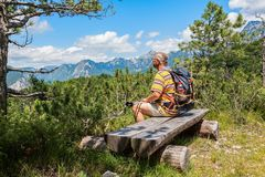 Hiker about 60 years old watching the Alpine panorama. Mature hiker about 60 years old. Walker in rest . Rambler watching the Mountain panorama. Active Stock Photography