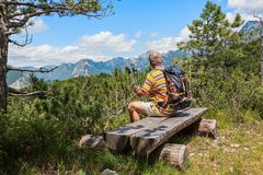 Hiker about 60 years old watching the Alpine panorama. Mature hiker about 60 years old. Walker in rest . Rambler watching the Mountain panorama. Active Stock Photo
