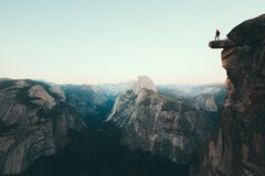 Hiker in Yosemite National Park, California, USA. A fearless hiker is standing on an overhanging rock enjoying the view towards famous Half Dome at Glacier Point stock photo