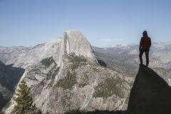 Hiker in Yosemite National Park, California, USA. A young hiker is standing on a rock enjoying the view towards famous Half Dome at Glacier Point in beautiful royalty free stock photography