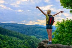 Hiker young girl standing with hands up achieving the top, admiring mountain landscape. Epic shot of hiking with cloudy sky, freedom success concept stock photos