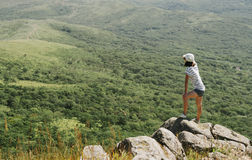 Hiker young woman standing on peak of rock Stock Photo