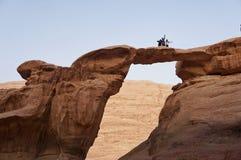 Hikers вверху гора в пустыне празднуя стоковые фото
