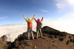 Hikers веселя к восходу солнца на горном пике Стоковая Фотография RF