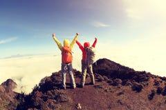 2 hikers веселя к восходу солнца на горном пике Стоковые Изображения