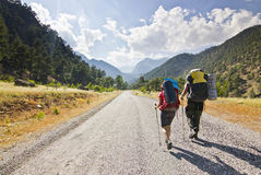 2 hikers в горах индюка идя на дорогу с рюкзаками Стоковое Изображение