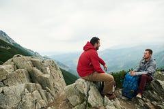 Hikers говоря совместно на горном пике Стоковое Фото