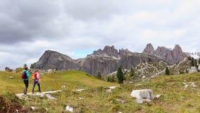 Hikers девушек идя близко Cinque Torri возвышаются