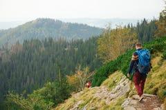 Hikers делая их путь вниз с скалистого следа в горах Стоковое Изображение RF