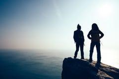 Hikers женщин смотря взгляд на утесе верхней части горы взморья окаймляются Стоковое Изображение RF