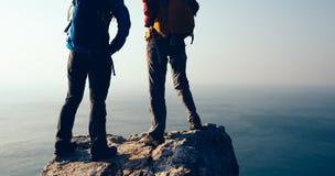 Hikers женщин смотря взгляд на утесе верхней части горы взморья окаймляются Стоковые Фотографии RF