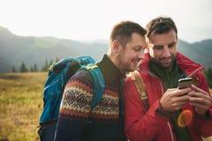 Hikers используя gps пока вне trekking в глуши Стоковая Фотография