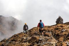 2 Hikers идя на наклон горы к каменным башням Стоковые Изображения RF