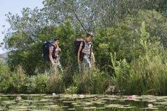 Hikers идя озером стоковые фото