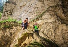 Hikers кладя в коробку на скале горы Стоковое Изображение RF