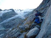 Hikers на высокогорном ледниковом озере гор на верхней части горы в Швейцарии Стоковые Фотографии RF