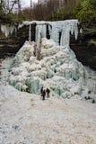 Hikers на основании замороженного каскада падают Стоковая Фотография RF