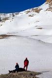 2 hikers на остановке в горах снега Стоковое Изображение