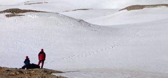 2 hikers на остановке в снежной горе Стоковые Фотографии RF