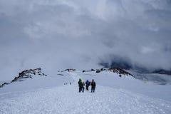 Hikers на снежной горной тропе Стоковые Изображения