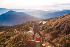 2 Hikers на следе в женщине гор наслаждаясь сценарным взглядом Стоковое фото RF