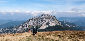 Hikers на холме Stoh с скалистым холмом Velky Rozsutec в горах Mala Fatra Стоковая Фотография