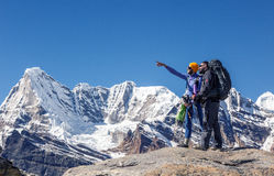 Hikers обсуждая перемещение направляют в высоких горах указывая рука Стоковая Фотография