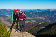 2 Hikers оставаясь на высоком утесе и горном виде с осенним лесом Стоковое фото RF