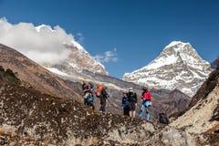 Hikers оставаясь на утесе против долины и пиков горы Стоковые Изображения