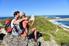 Hikers ослабляя после прогулки восхищая вид на море Стоковые Изображения RF