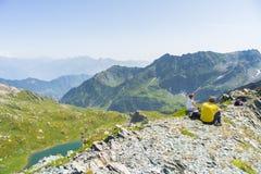 Hikers отдыхая на саммите горы, экспансивной панораме Стоковые Фотографии RF