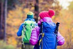 Hikers пар человека и женщины счастливые идя в древесины осени Стоковые Фото