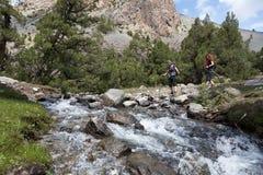 2 hikers пересекая быстро пропуская реку Стоковая Фотография