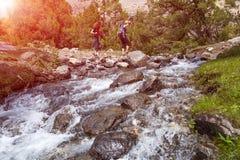 2 hikers пересекая быстро пропуская реку Стоковые Изображения RF