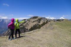 Hikers пешего †«идя на поход в природе горы и указывая на горный пик, на солнечный день Стоковое Изображение RF