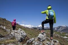 Hikers пешего †«идя на поход в природе горы и указывая на горный пик, на солнечный день Стоковые Изображения RF