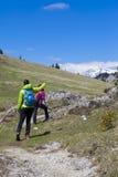 Hikers пешего †«идя на поход в природе горы и указывая на горный пик, на солнечный день Стоковая Фотография RF